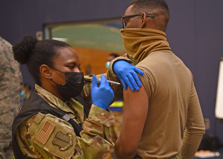 U.S. Air Force Lt. Col. Cynthia Ennis, 17th Medical Group command staff healthcare integrator, administers the first COVID-19 vaccine to Airman 1st Class Earl Newton, 17th Security Forces Squadron entry controller, at the immunization clinic inside the Mathis Fitness Center on Goodfellow Air Force Base, Texas, Jan. 20, 2021. Newton volunteered for the first round of COVID-19 vaccinations, which were distributed to Goodfellow personnel based on a predetermined priority. (U.S. Air Force photo by Senior Airman Abbey Rieves)