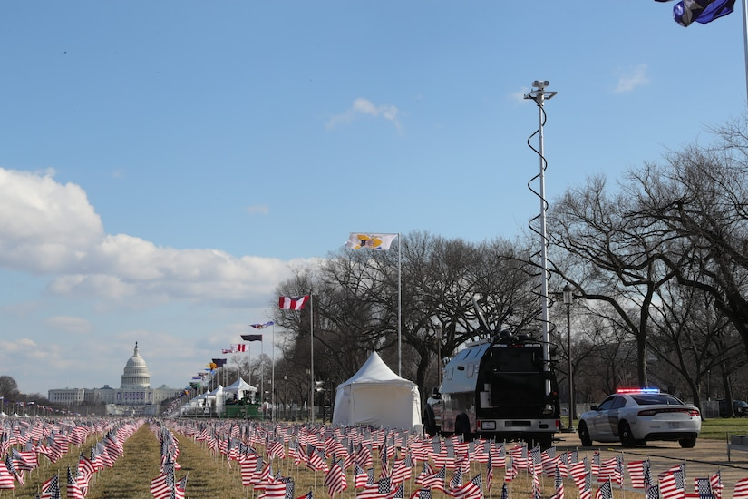 A tactical command vehicle parks near the U.S. Capitol beside a field of American flags.