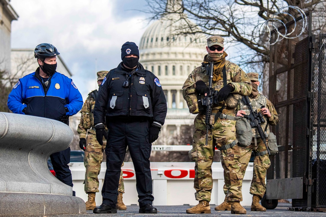 Guardsmen stand in front of the U.S. Capitol.