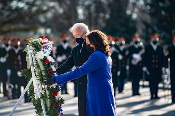 A woman and an older man put their hands on a large wreath that sits on a stand.
