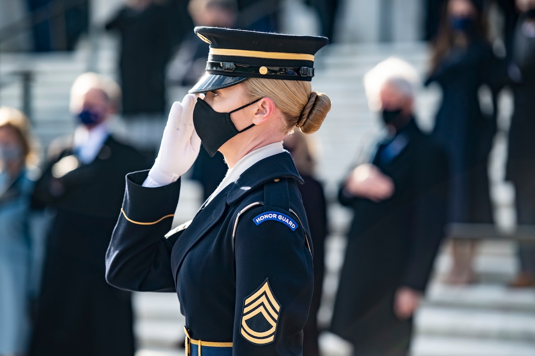 A soldier salutes at an outdoor ceremony.