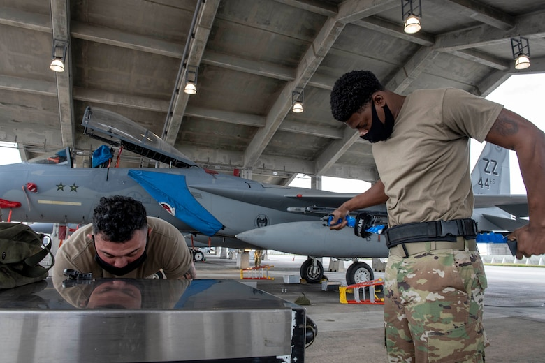 The 44th Aircraft Maintenance Unit load crew members prepare for the quarterly weapons load competition at Kadena Air Base, Japan, Jan. 14, 2021. This competition featured two teams competing for the 18th Wing's best load crew. (U.S. Air Force photo by Naoto Anazawa)