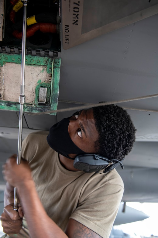 U.S. Air Force Senior Airman Tyree Singleton, 44th Aircraft Maintenance Unit weapons load crew member, tightens a screw during the quarterly weapons load competition at Kadena Air Base, Japan, Jan. 14, 2021. Weapons load crew competitions are held each quarter and annually in order to boost morale and highlight superior performers among the load crew teams. (U.S. Air Force photo by Naoto Anazawa)
