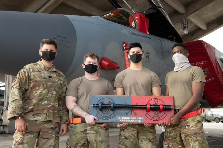 U.S. Air Force Lt. Col. Gerard Carisio, the 18th Maintenance Group deputy commander, and load crew members from the 67th Aircraft Maintenance Unit pose with the load competition trophy in front of an F-15C Eagle at Kadena Air Base, Japan, Jan. 15, 2021. The 67th AMU won the quarterly load competition against the 44th AMU. (U.S. Air Force photo by Airman First Class Stephen Pulter)