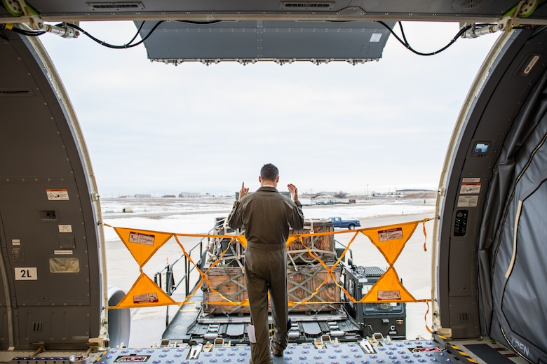 Tech. Sgt. Chris Davis, a boom operator from the 916th Air Refueling Wing, marshals a Tunner 60K aircraft cargo loader during a training exercise, Jan 10, 2021, at Hill Air Force Base, Utah.