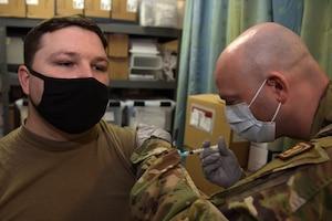 An Airmen receives a shot.
