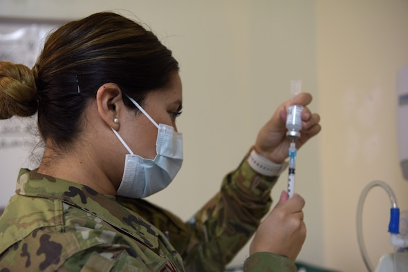 An Airman fills a shot vial