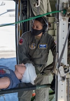 Senior Airman Emilie Canlas, flight medic for the 36th Aeromedical Evacuation Squadron, awaits the cue to raise the litter during a pre-deployment exercise at Keesler Air Force Base, Miss., Jan. 13, 2021. Canlas volunteered early during the COVID-19 pandemic to deploy and assist with the transport and care of COVID-19 patients.(U.S. Air Force photo by Senior Airman Kristen Pittman)