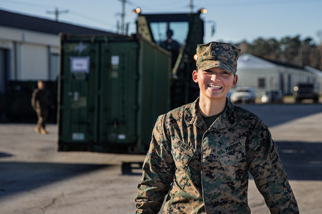 """U.S. Marine Corps Sgt. Anthonette Bement, an embarkation specialist with the 26th Marine Expeditionary Unit, ground guides a forklift at Camp Lejeune, North Carolina, Dec. 10, 2020. """"If I don't do my job correctly, gear won't get shipped out in a timely manner, and if anything is late, things get left behind,"""" said Bement. """"If gear is left behind, Marines won't be prepared."""" Embarkers have a vital role during deployments. They are responsible for ensuring gear, vehicles, and other mission-essential equipment abide by applicable local and international shipping rules and ultimately reach their destination successfully. (U.S. Marine Corps photo by Cpl. Armando Elizalde)"""