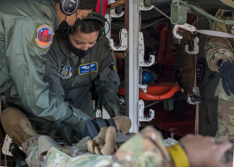 Capt. Toya Williams, 36th Aeromedical Squadron flight nurse, and Senior Airman Emilie Canlas, 36th AES flight medic, work together to secure a patient's litter during pre-deployment aeromedical evacuation training at Keesler Air Force Base, Miss., Jan. 13, 2021. The 36th AES is part of the Air Force Reserve's 403rd Wing. (U.S. Air Force photo by Senior Airman Kristen Pittman)