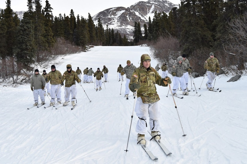 Soldiers ski in the mountains.