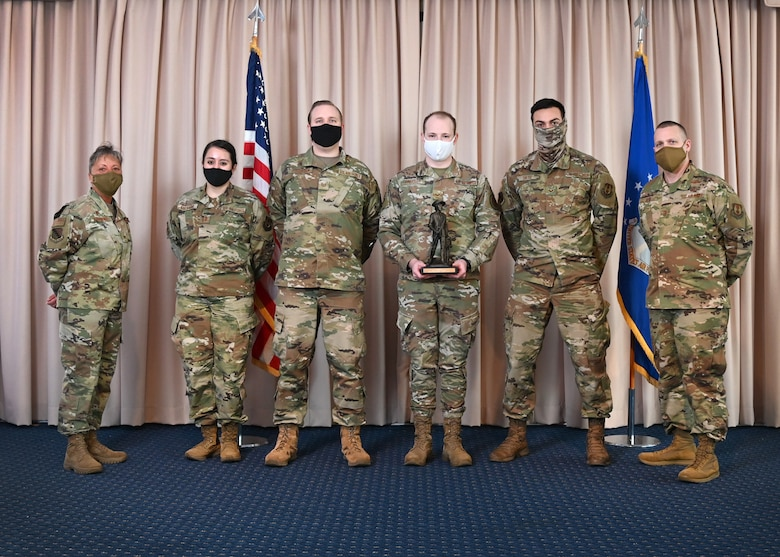 Col. Katrina Stephens, 66th Air Base Group commander, and Chief Master Sgt. Bill Hebb, 66 ABG command chief, present the 66th Medical Squadron Public Health team with the 2020 Small Team of the Year award at Hanscom Air Force Base, Mass., Jan 20.