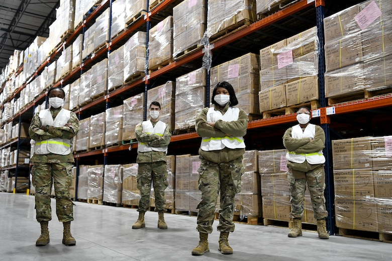 Four service members pose for a group portrait inside a medical supply warehouse.