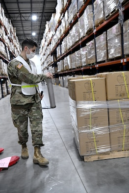 An Airmen uses plastic wrap to palletize supplies.