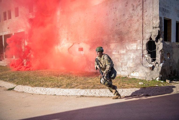 A soldiers runs while carrying a weapon near a cloud of red smoke.