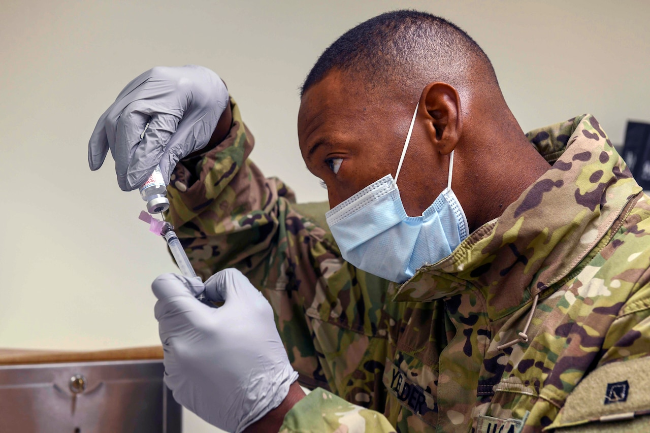 A soldier wearing a face mask and gloves fills a syringe with a dose of  COVID-19 vaccine.