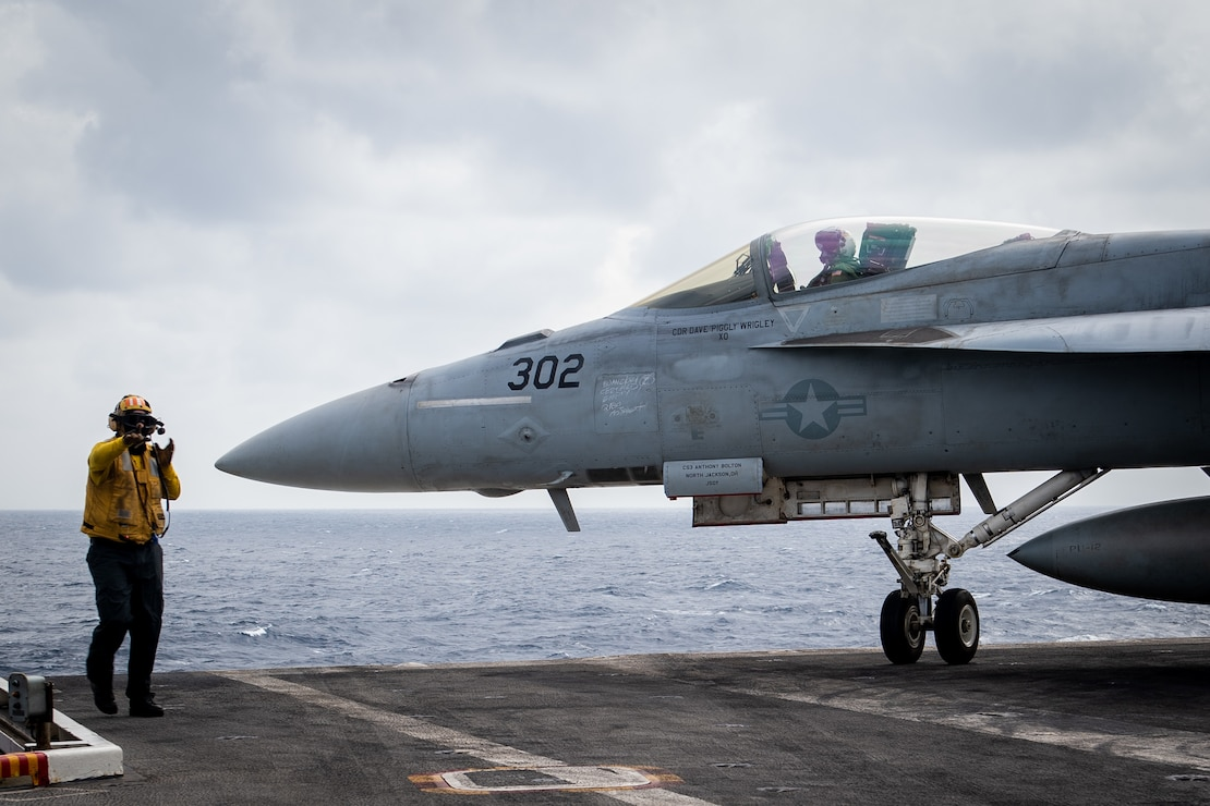 "Aviation Boatswain's Mate (Handling) 1st Class Jeremy Gould, from Goodland, Kan., directs the pilot of an F/A-18E Super Hornet, assigned to the ""Blue Diamonds"" of Strike Fighter Squadron (VFA) 146, on the flight deck of the aircraft carrier USS Theodore Roosevelt (CVN 71)."