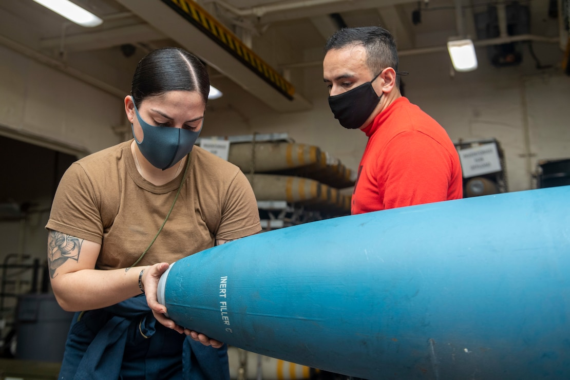 Aviation Ordnanceman Airman Mariangelys Ojeda Marrero, left, from Puerto Rico, assigned to the forward-deployed amphibious assault ship USS America (LHA 6), inserts a nose plug into an inert practice bomb, while Aviation Ordnanceman 2nd Class Rafael Gonzalez Borras, from Miami, also assigned to America, supervises.