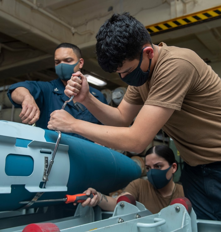 Aviation Ordnancemen assigned to the forward-deployed amphibious assault ship USS America (LHA 6), fasten stabilizing fins on an inert practice bomb.