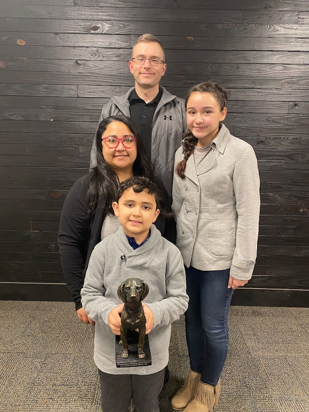 """U.S. Air Force Master Sgt. Brandon Mitcheltree, his wife Monica and their children, present their """"Heart of Downtown"""" trophy they received from Warrensburg Main Street Inc. for their community volunteer efforts, Jan. 14, 2021, in Warrensburg, Mo. Mitcheltree is the 509th Bomb Wing Inspector General superintendent at Whiteman Air Force Base. (Courtesy photo by Warrensburg Main Street Inc.)"""