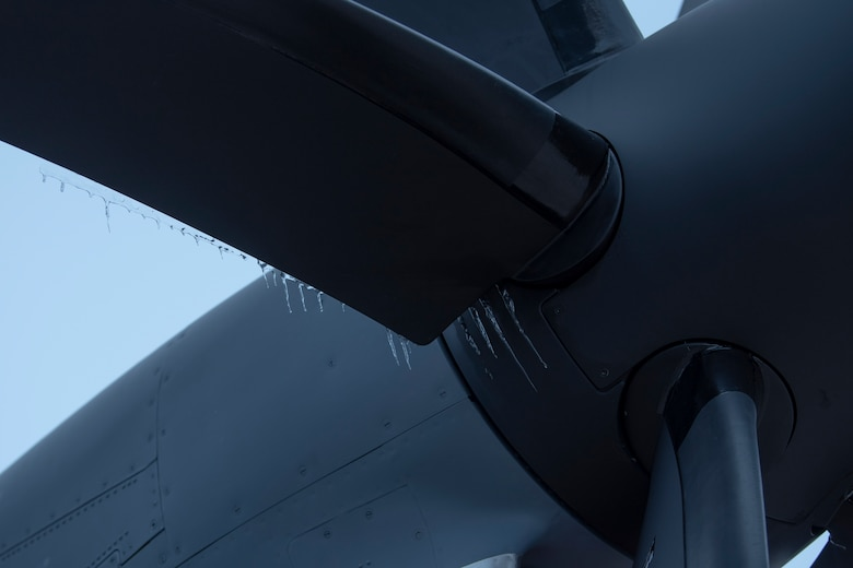 Icicles hang down from the propeller of an airplane