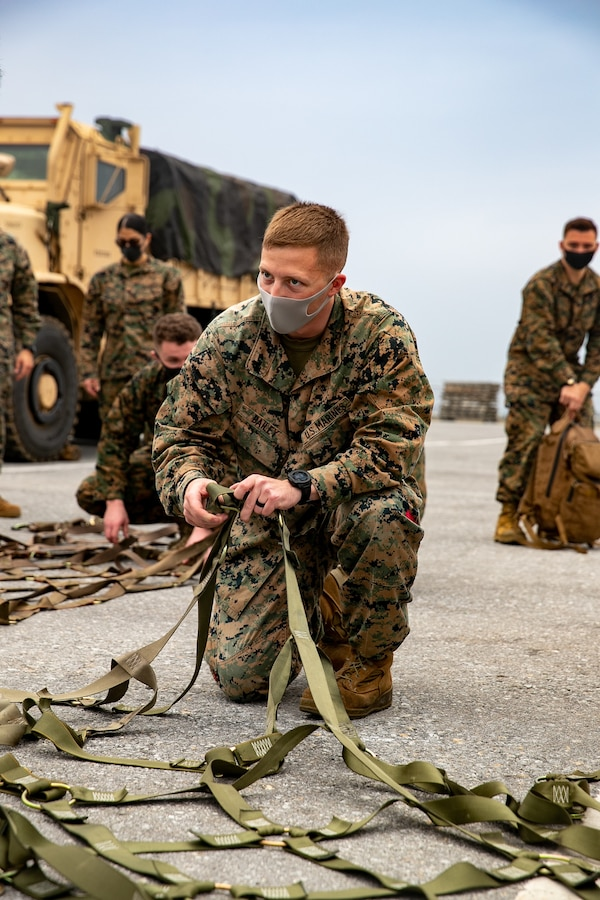 U.S. Marine Corps Cpl. Ashton Bailey, a landing support specialist with 3rd Landing Support Battalion, 3rd Marine Logistics Group, adjusts the nets for palletized gear during deployment preparation on Kadena Air Force Base, Okinawa, Japan, Jan. 21, 2021. 3rd MEB practices distributed operations as part of the Marine Corps' only forward-deployed force. (U.S. Marine Corps photo by Lance Cpl. Natalie Greenwood)