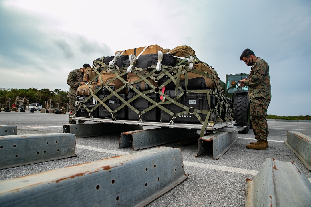 U.S. Marines with 3rd Landing Support Battalion, 3rd Marine Logistics Group, weigh palletized gear during deployment preparation on Kadena Air Force Base, Okinawa, Japan, Jan. 21, 2021. 3rd MEB practices distributed operations as part of the Marine Corps' only forward-deployed force. (U.S. Marine Corps photo by Lance Cpl. Natalie Greenwood)