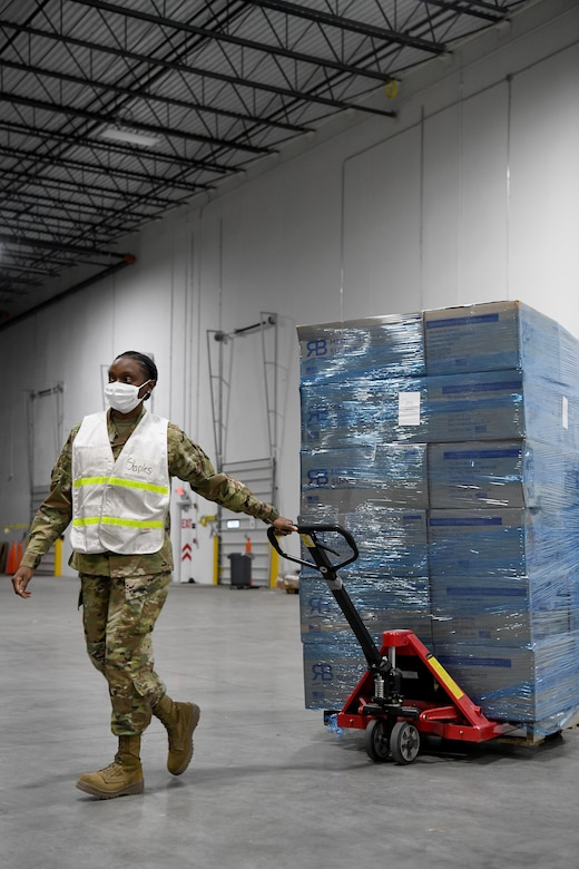 An Airman transports a pallet of medical supplies in a warehouse.