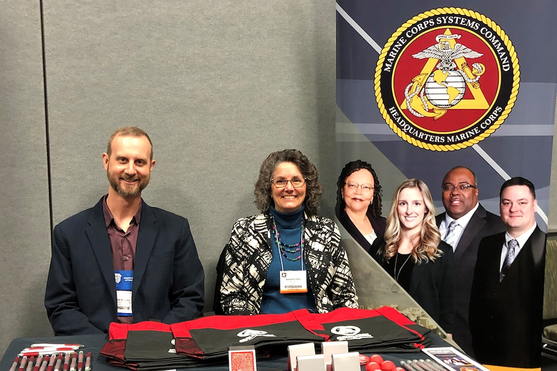 The division head for Marine Corps Systems Command's Manpower and Services and an assistant program manager for the Program Manager for Training Systems, impart information about Human Resources to passersby in Orlando, Fla., Dec. 6.