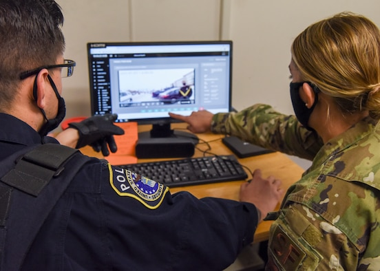 Department of Defense Police Officer Richard Martinez, patrol officer with the 673d Security Forces Squadron and U.S. Air Force Senior Airman Danielle Chose, a 673 SFS operations support/police services operator, review footage from a new body camera after an incident Jan. 8, 2021, at Joint Base Elmendorf-Richardson, Alaska. The 673d SFS has begun integrating 60 new, high-tech body cameras into daily operations after the adaptable technology reached a point of not only being a reliable safety and training instrument, but a multifunctional accountability tool serving all. (U.S. Air Force photo by Senior Airman Crystal A. Jenkins)