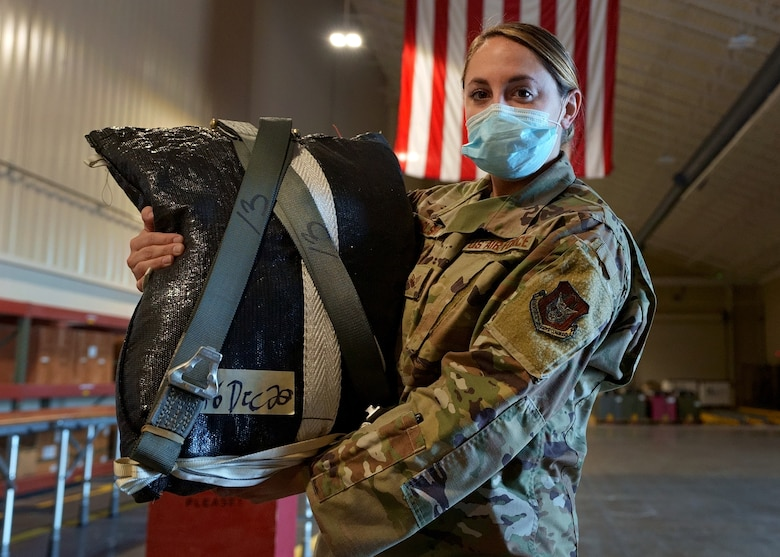 Staff Sgt. Makenzie Carlson, 919th Special Operations Logistic Readiness Squadron air transportation specialist, poses with a freshly packed parachute at Duke Field, Florida, Dec. 29, 2020.