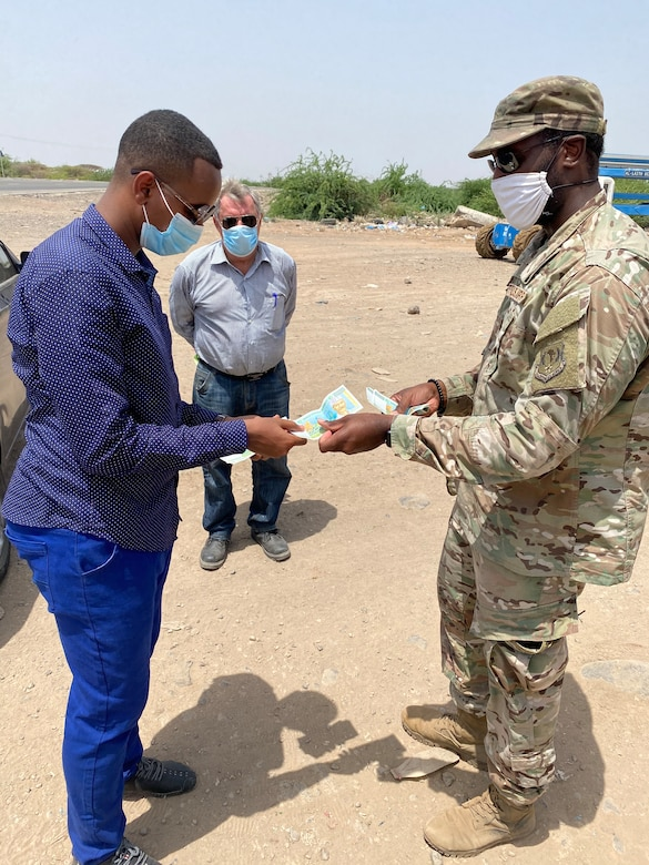 A photo of an Airman exchanging money with a Djiboutian national.