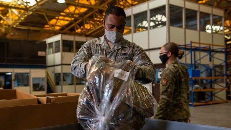 A logistics Airman sorts body armor vests into boxes.