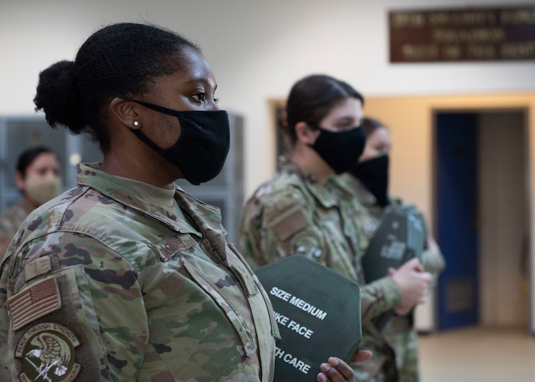 Several women security forces Airmen stand in-line while holding armor plates
