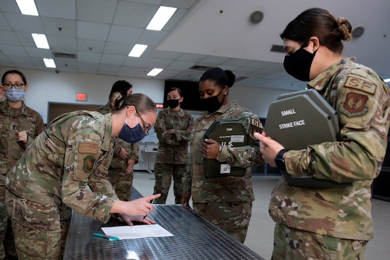 Women security forces Airmen line-up at a table to be issued new armored vests.