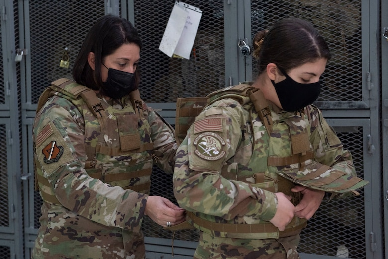 An older woman helping an younger woman don a armored vest.