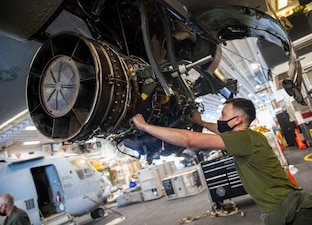 A Marine works on an Osprey aircraft engine.