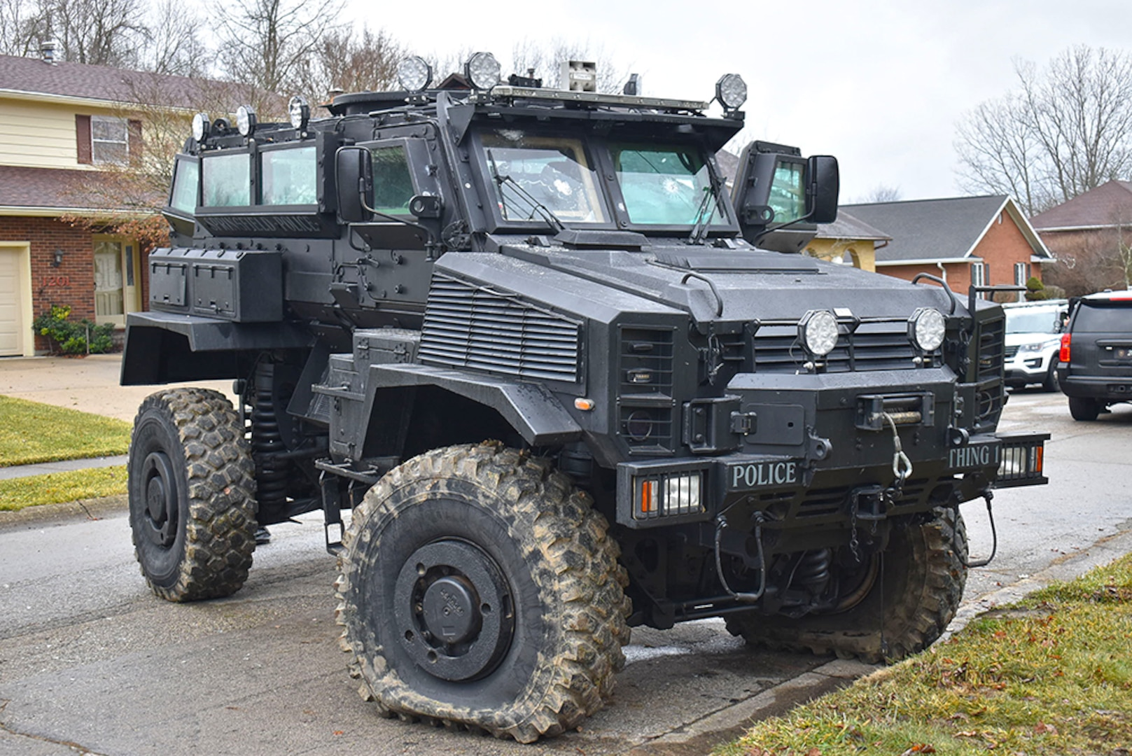 An MRAP with bullet marks and flat front tires is parked on a residential street.