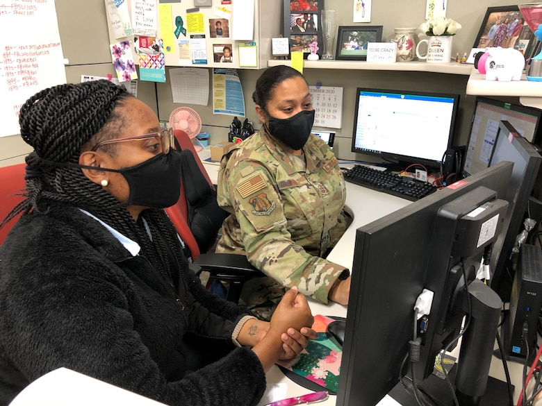 Senior Master Sgt. Erica White, a mobilization analyst assigned to the Agile Combat Support Branch, trains Sarah Johnson, a newly hired deployment readiness planning specialist.