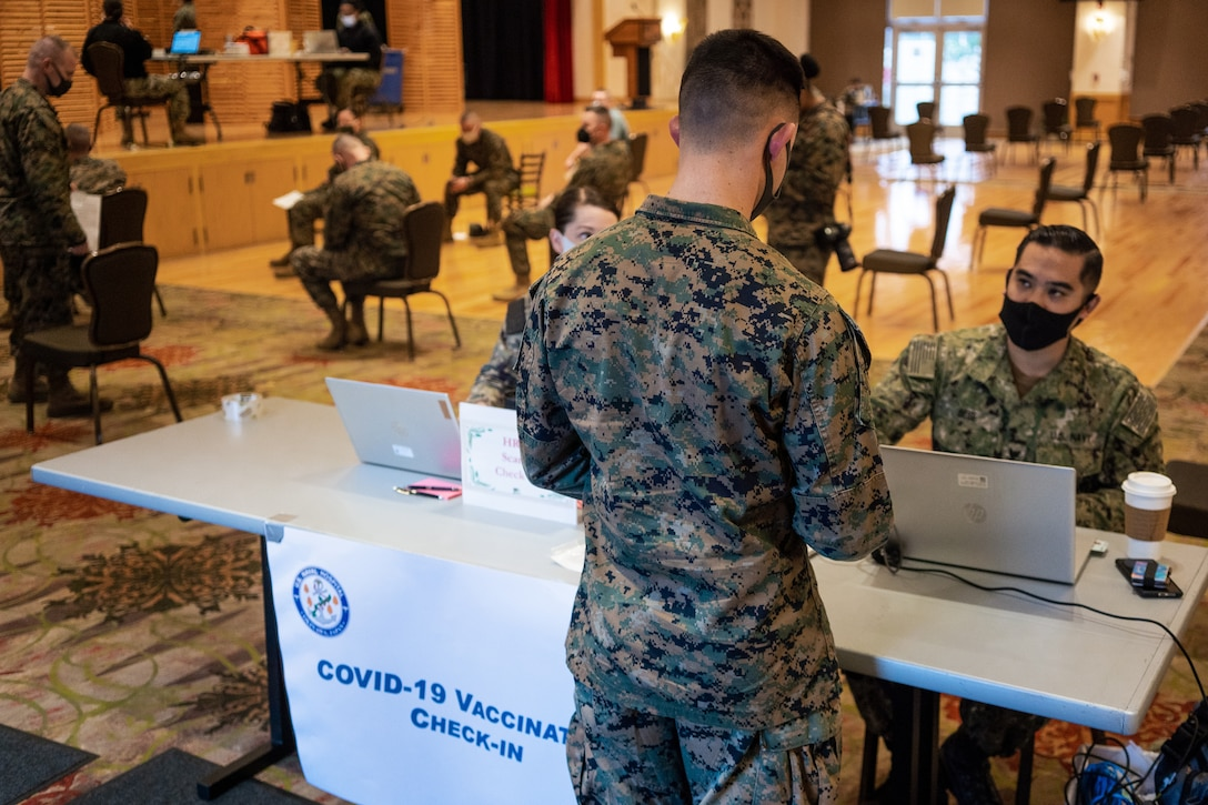 A Marine stands at a table to check in for his COVID-19 vaccination.