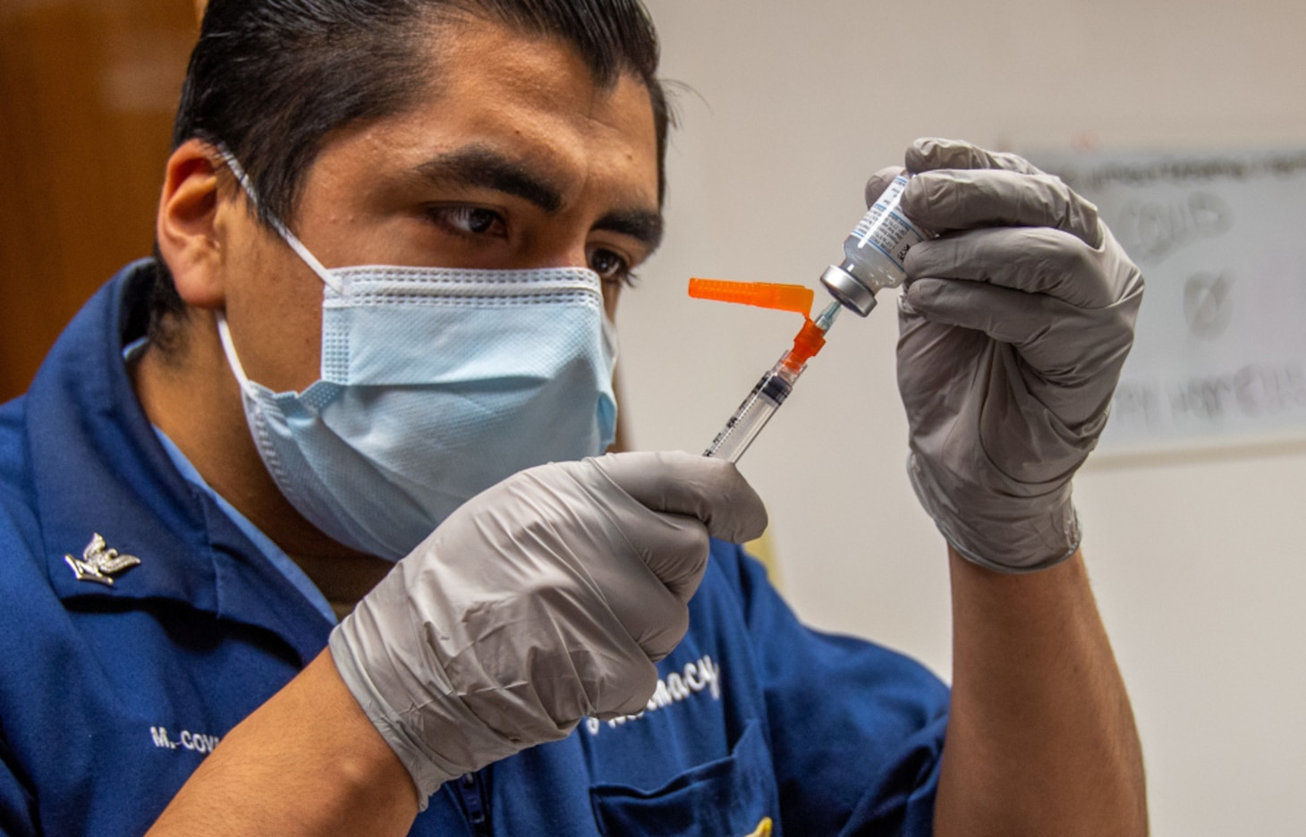 NAVAL STATION ROTA, Spain (Jan. 15, 2021) Hospital Corpsman 3rd Class Martin Covarrubias draws vaccine into a syringe from a vial from the first coronavirus (COVID-19) vaccine shipment to U.S. Naval Hospital (USNH) Rota, Spain on 15 January, 2021. The vaccine will be administered in phases based on priority levels to reduce the burden of COVID-19 in high-risk populations and simultaneously mitigate risk to military operations. (U.S. Navy photo by Mass Communication Specialist 1st Class Nathan Carpenter)