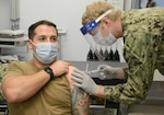 210111-N-AZ866-0130 NAVAL SUPPORT ACTIVITY SOUDA BAY, Greece (Jan. 11, 2021)  Hospital Corpsman 3rd Class Zak McBride receives the Moderna COVID-19 vaccine from Hospital Corpsman 3rd Class Caleb Newbill at the Branch Health Clinic Souda Bay, Jan. 11, 2021. The vaccine is being administered in phases based on DoD priority levels to reduce the burden of COVID-19 in high-risk populations and simultaneously mitigate risk to military operations. McBride a native of Ellington, Conn. Newbill is a native of Covington, Tenn. NSA Souda Bay is an operational ashore base that enables U.S., allied, and partner nation forces to be where they are needed when they are needed to ensure security and stability in Europe, Africa, and Southwest Asia. (U.S. Navy photo by Mass Communication Specialist 2nd Class Kelly M. Agee/Released)