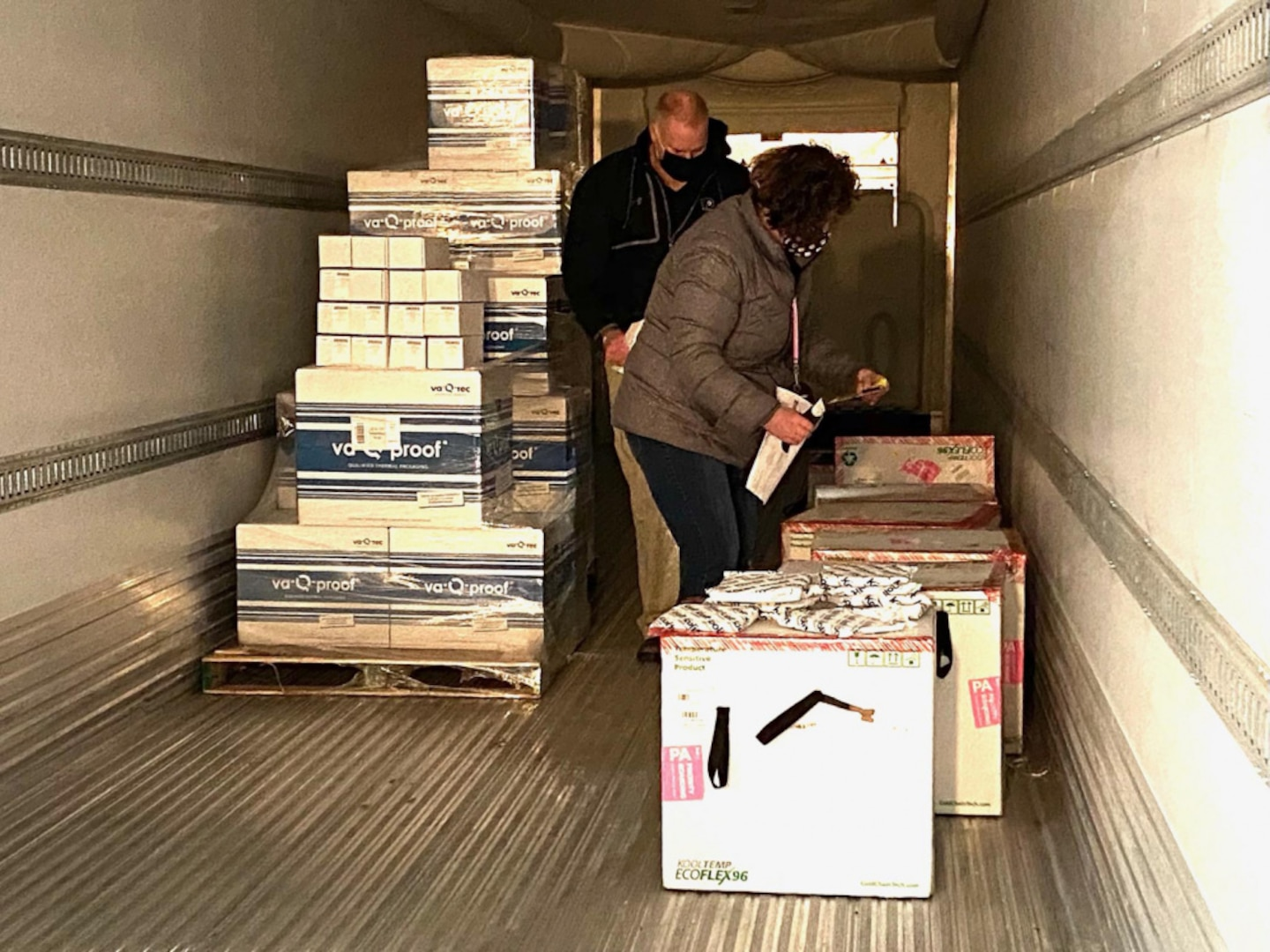 Defense Logistics Agency Distribution Susquehanna employees-Jenny Potts and George Hillman inspect Moderna COVID-19 packages inside the cold storage unit as the vaccines are prepared for shipment to overseas troops and the Navy Fleet.