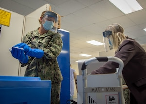 Lt. Devon Graham, Naval Medical Center San Diego's (NMCSD) material management division officer (left), and Tracey Lopez, NMCSD's immunizations program director (right), pack a box with dry ice in the hospital's laboratory.