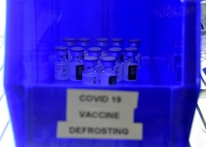 A blue container of vials labeled COVID-19 Vaccine Defrosting sits center frame.