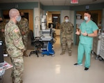 Army Lt. Gen. Ronald Place, Director, Defense Health Agency, talks with Spc. Aaron Neuenschwander, health care specialist, at Brooke Army Medical Center, Joint Base San Antonio-Fort Sam Houston Jan. 20, 2021.