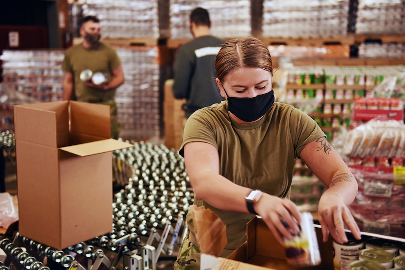 A soldier wearing a face mask helps prepare pallets of food orders for distribution to the community.