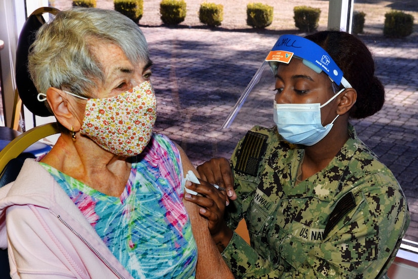 A soldier wearing a face mask administers a COVID-19 vaccine to an elderly woman.