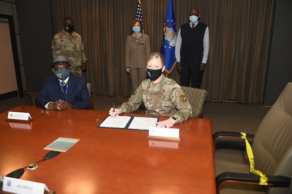 Photo shows man and woman sitting at table signing papers.