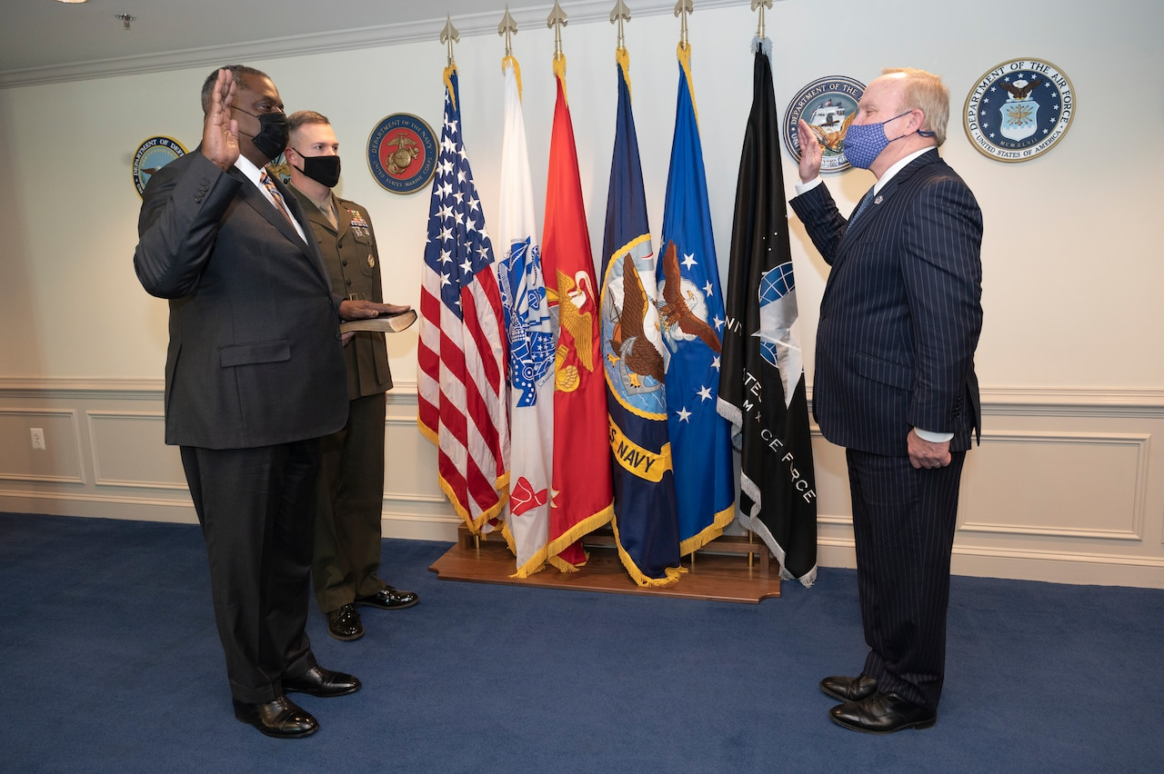 Secretary of Defense Lloyd J. Austin III stands next to a man holding up his right hand facing another man.